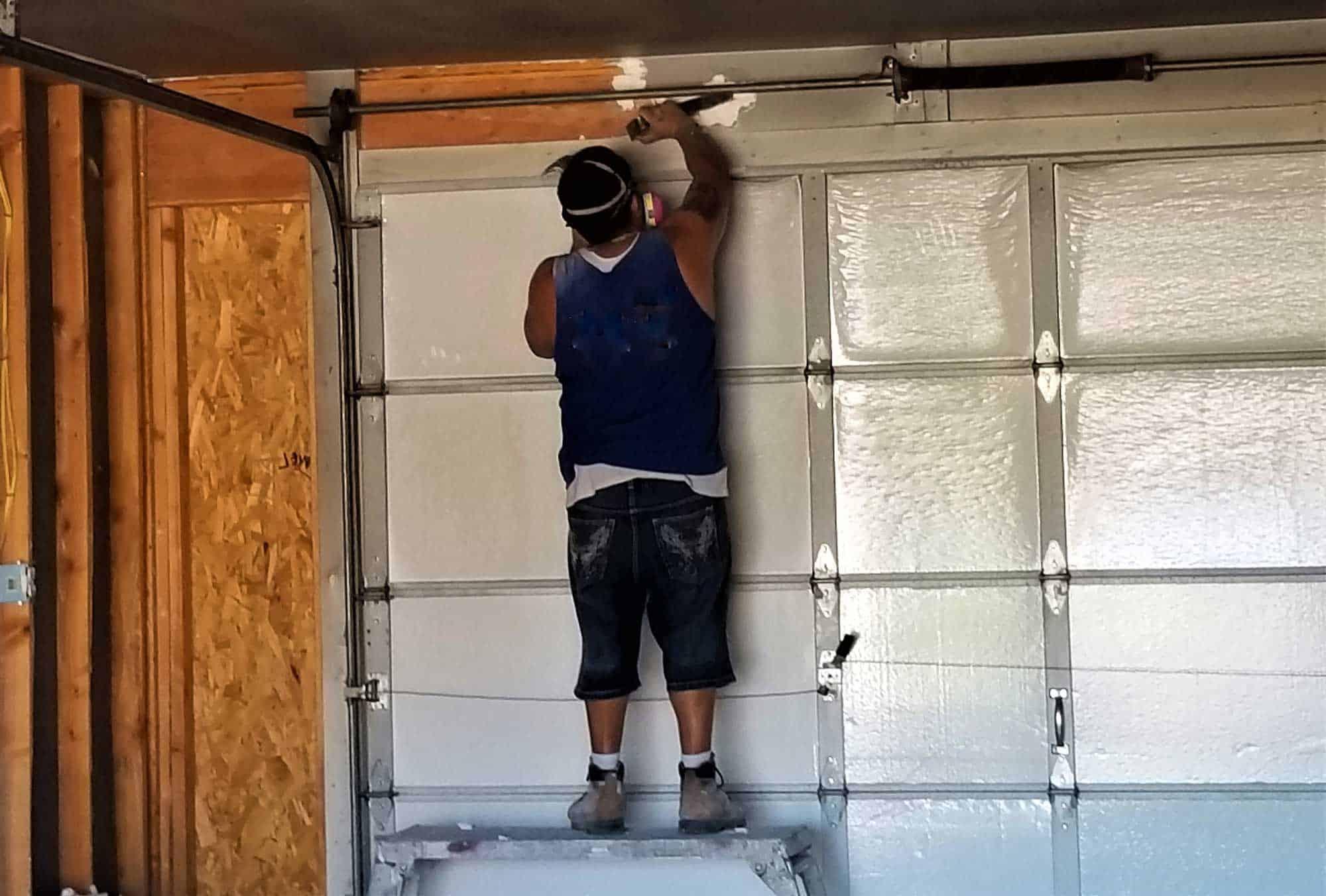 construction worker installing garage door spring