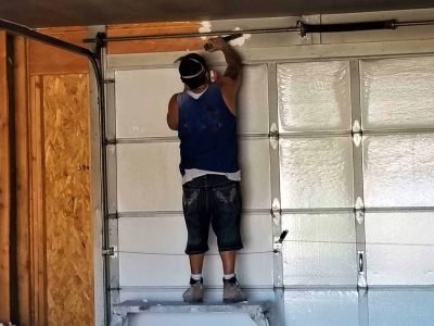 construction worker installing garage door spring