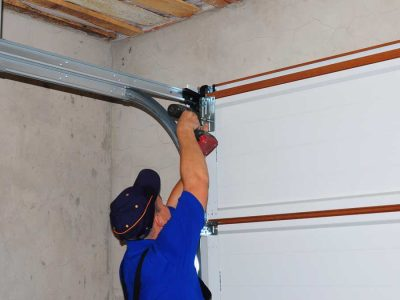 man repairing noisy garage door