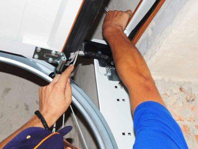 man repairing overhead garage door